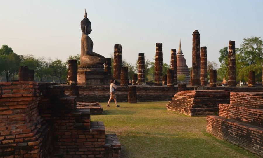 A woman walks Wat Mahathat temple in Thailand's Sukhothai Historical Park.