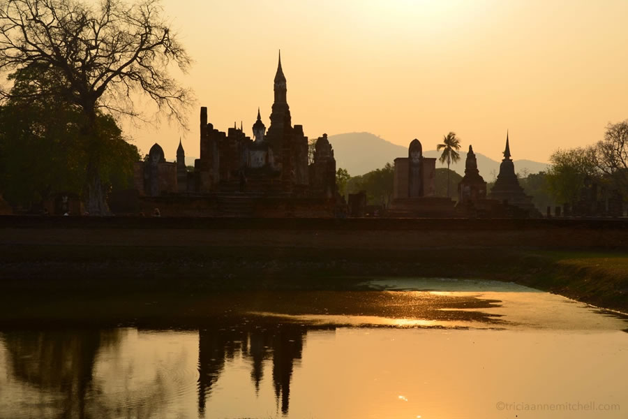 Wat Mahathat temple is reflected in water at sunset in Sukhothai Historical Park.
