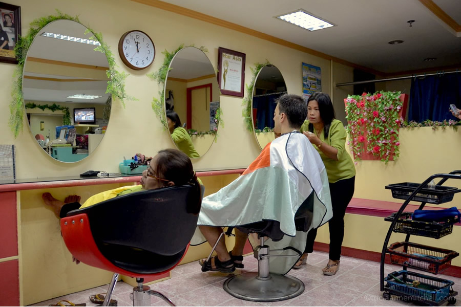 A woman cuts a man's hair in Tagbilaran, the Philippines.