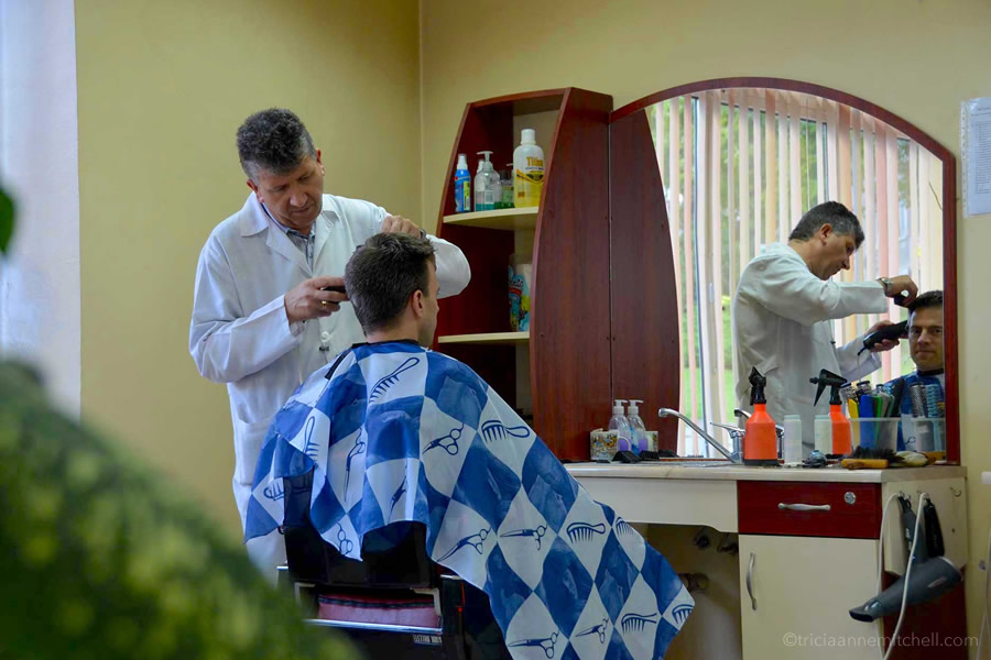A man cuts a man's hair in Veliko Tarnovo, Bulgaria.