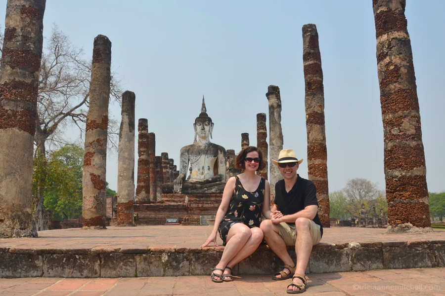 A couple sits in front of Sukhothai's Wat Mahathat.