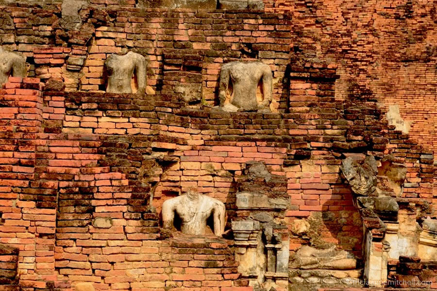 Buddha statues without heads adorn the exterior of Wat Phrapai Luang Temple in Sukhothai, Thailand.