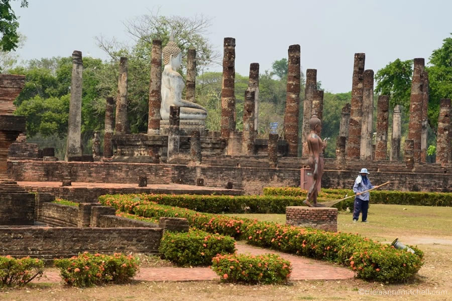 A woman rakes foliage at Wat Sa Si Temple in Sukhothai, Thailand.