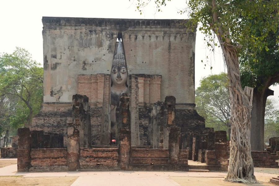 The Buddha inside Wat Si Chum temple seemingly peeks through the entrance.