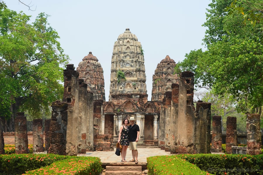 A man and woman stand in front of Wat Si Sawai in Sukhothai Historical Park.