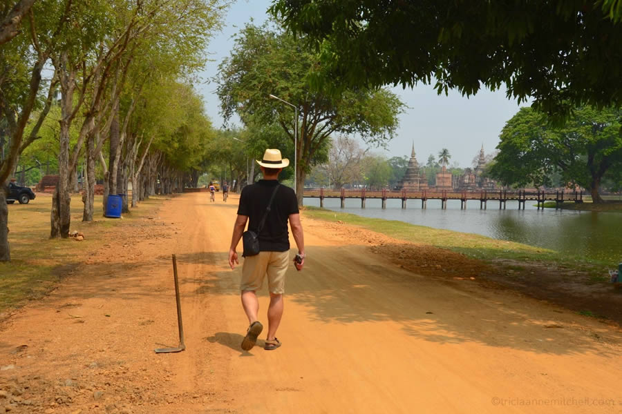 Man walking on dirt road in Sukhothai Historical Park.