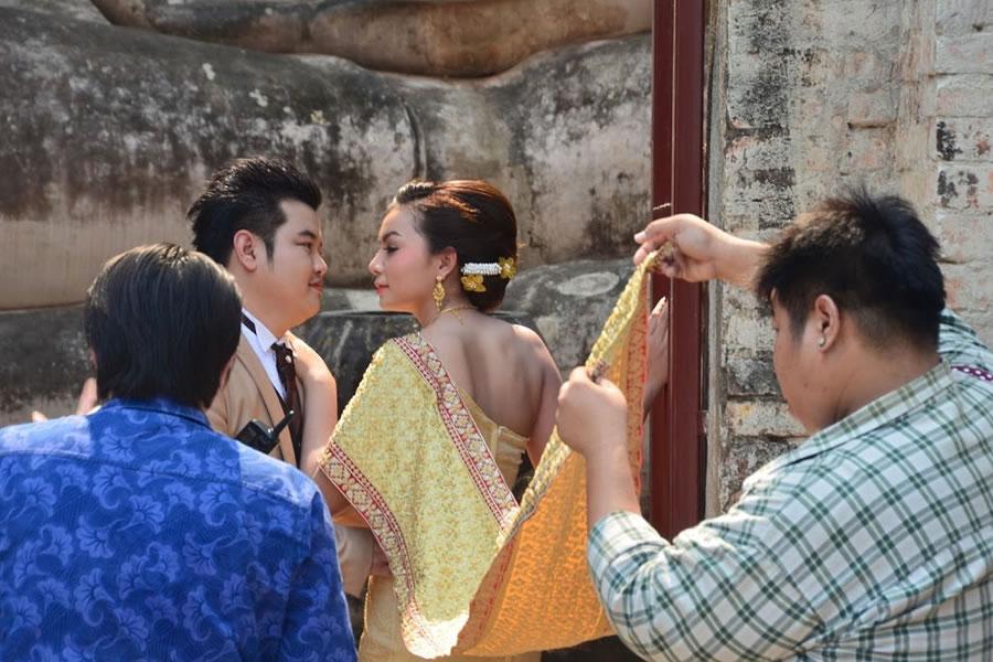 A wedding couple has their photo taken at Wat Si Chum Temple in Sukhothai, Thailand.