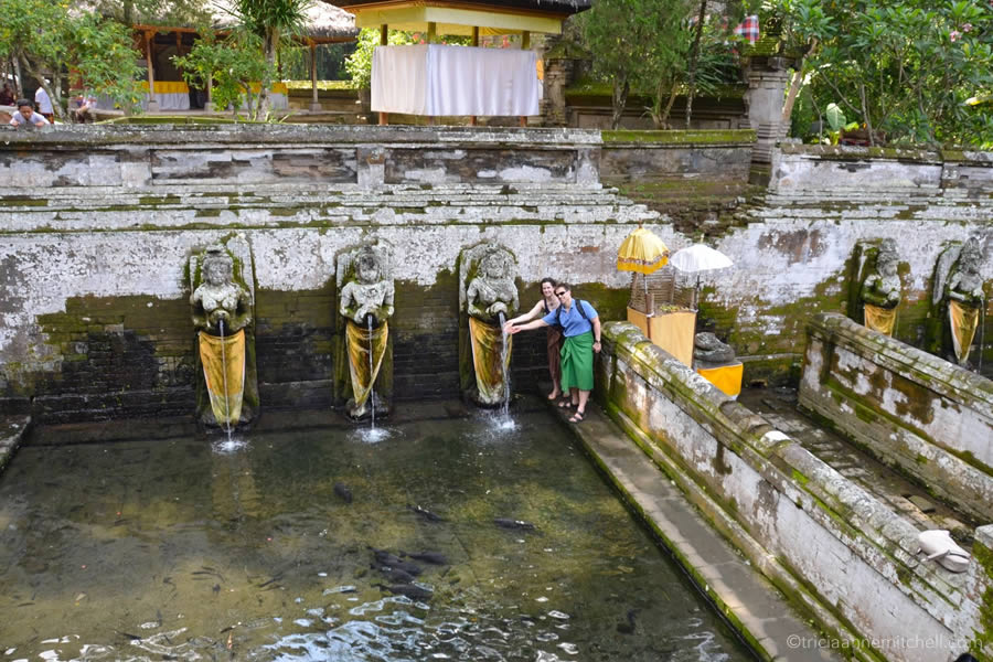 A couple stands next to the holy water spring at Bali's Elephant Cave (Goa Gajah).