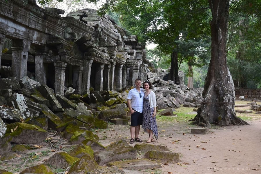 A couple stands beside the ruins of a Ta Prohm Temple in Cambodia.