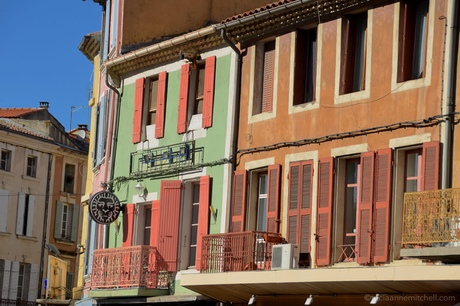 The exterior of colorful, shuttered homes in the city of Orange, France.