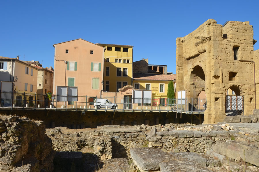 View of an Orange, France street scene through the fenced-in Roman Theater interior.