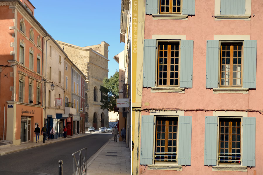A streetscape in Orange, France, and a pink building with blue shutters.