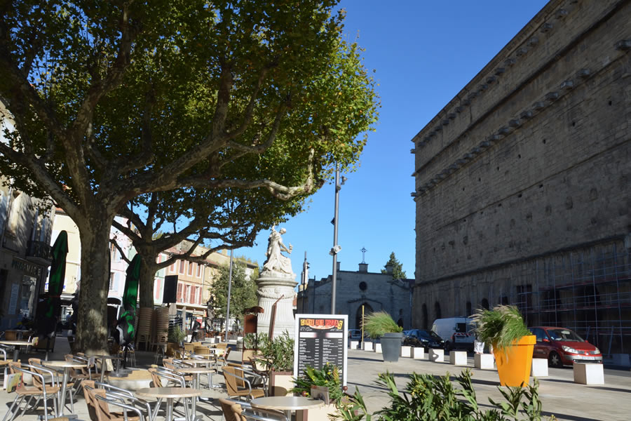 Cafe tables sit across from the Roman Theater in Orange, France.