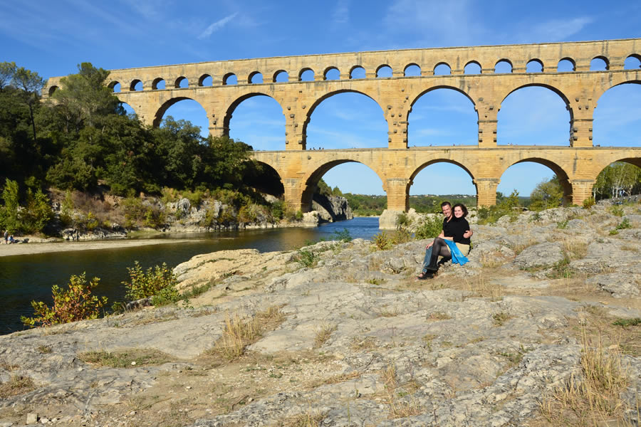 A couple sits in front of France's Pont du Gard aqueduct.