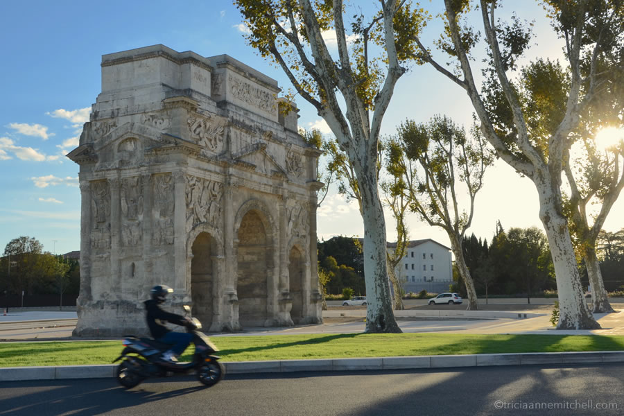 A person on a motorbike speeds past the Triumphal Arch of Orange, France.