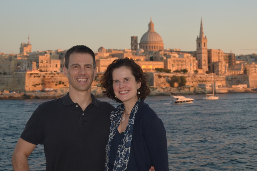 Shawn and Tricia standing in front of the Valletta skyline, in Malta.