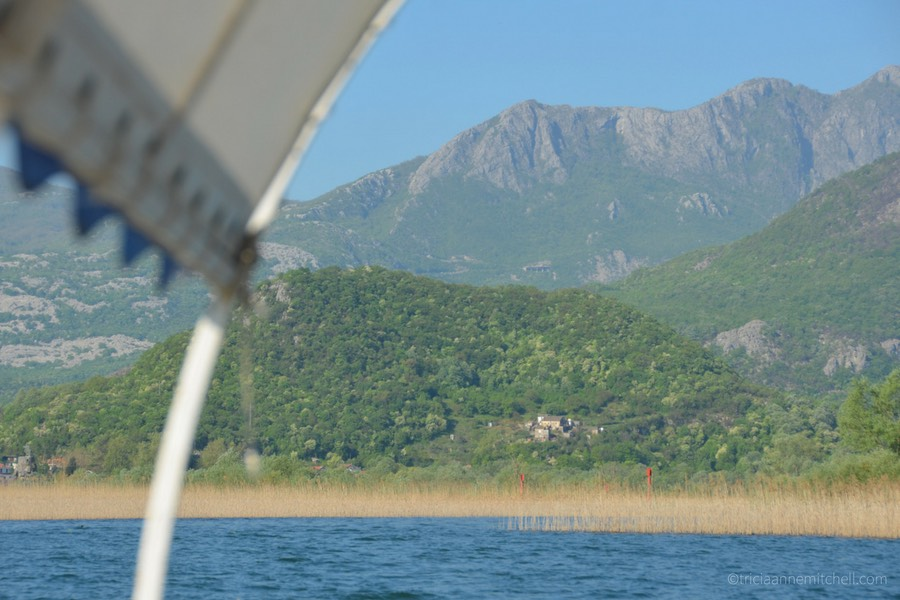 Rugged mountains and a forested hill fill the landscape by Lake Skadar.