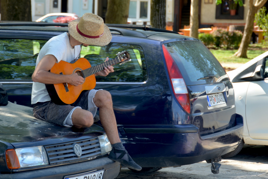 A man sitting on the front of a car plays guitar in a Virpazar parking lot, near Skadar Lake, Montenegro.