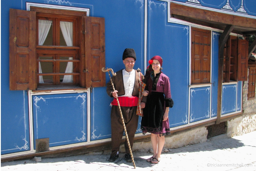 A man and woman, dressed in traditional Bulgarian clothing, stand next to a historic blue building in Koprivshtitsa, Bulgaria.