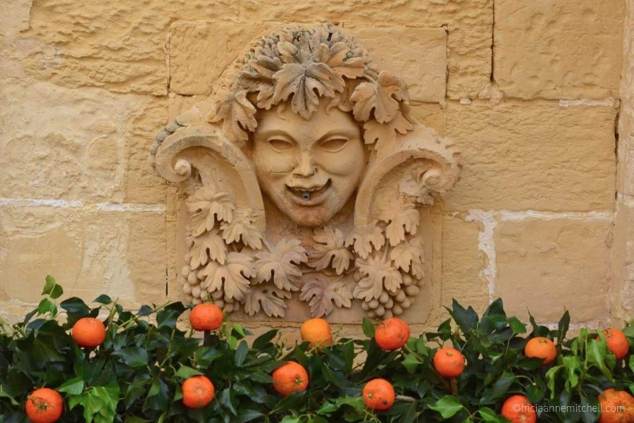 Oranges and greenery decorate a limestone fountain at the Citrus Festival at the San Anton Palace in Malta.