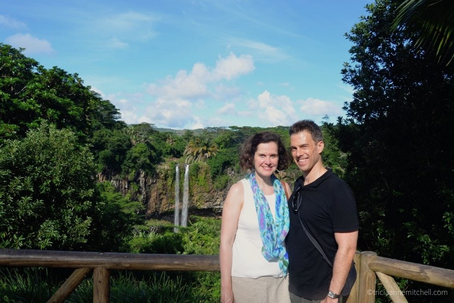 A couple stands overlooking the Chamarel Waterfalls, near the Terres des Sept Couleurs.