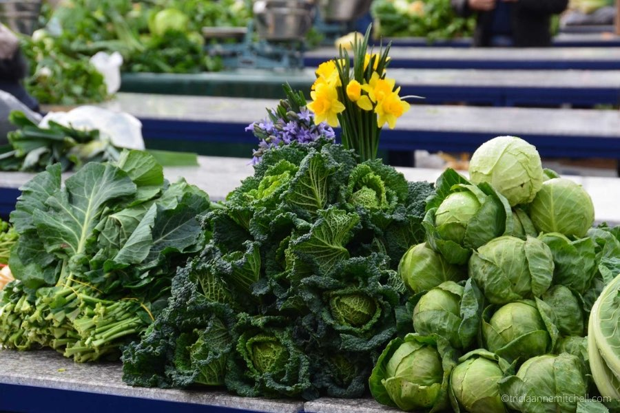 At the fresh market in Split, Croatia, spinach, kale, and cabbage sit on top of a vendor's table.