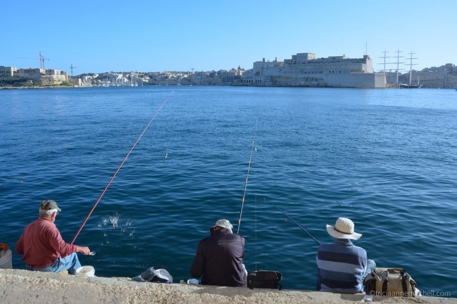 Three men fish in Valletta's Grand Harbour.