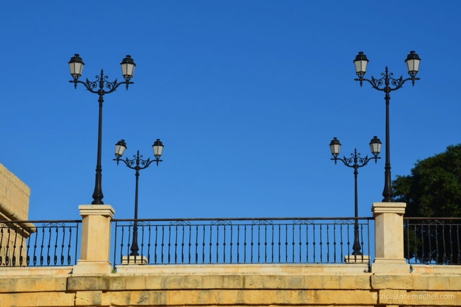 Four sets of Maltese lamp posts line a bridge.