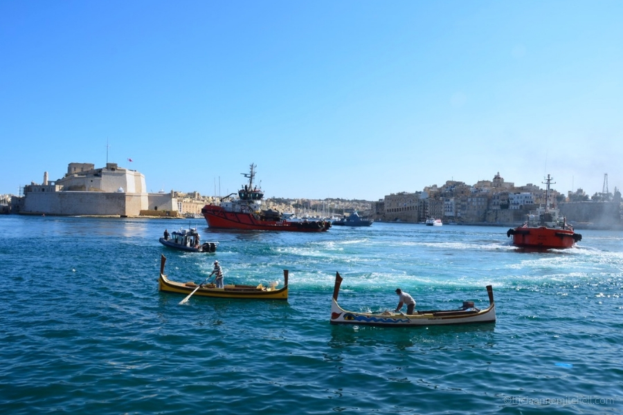 Dgħajsas and tugboats float in Valletta's Grand Harbour, with a blue sky overhead.