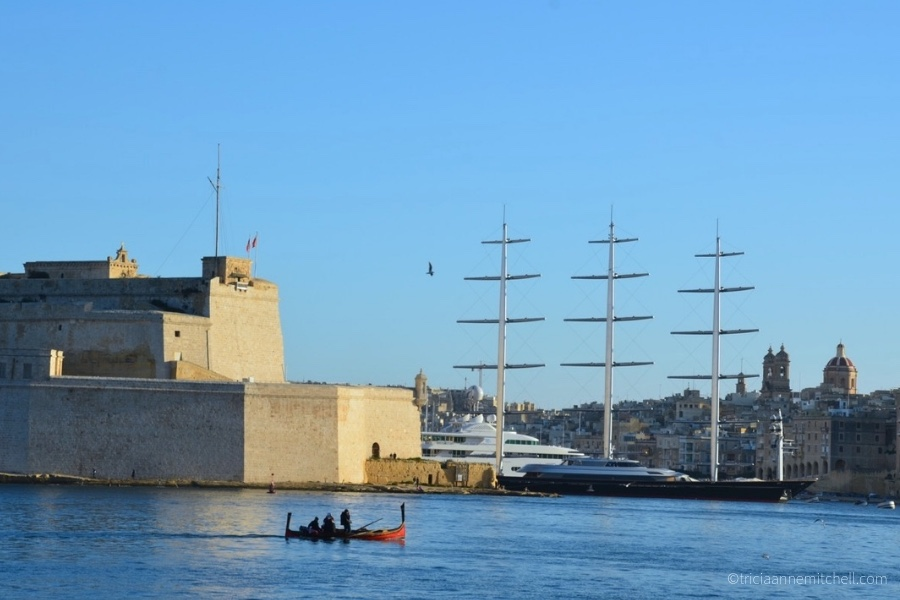 A tiny dgħajsa (a traditional Maltese boat) glides past a superyacht in Malta's Grand Harbour.