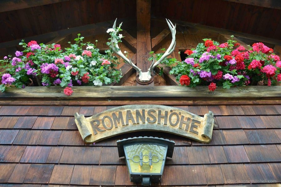 Close-up of a Bavarian restaurant. There are a pair of antlers, red and purple flowers, and a sign that says