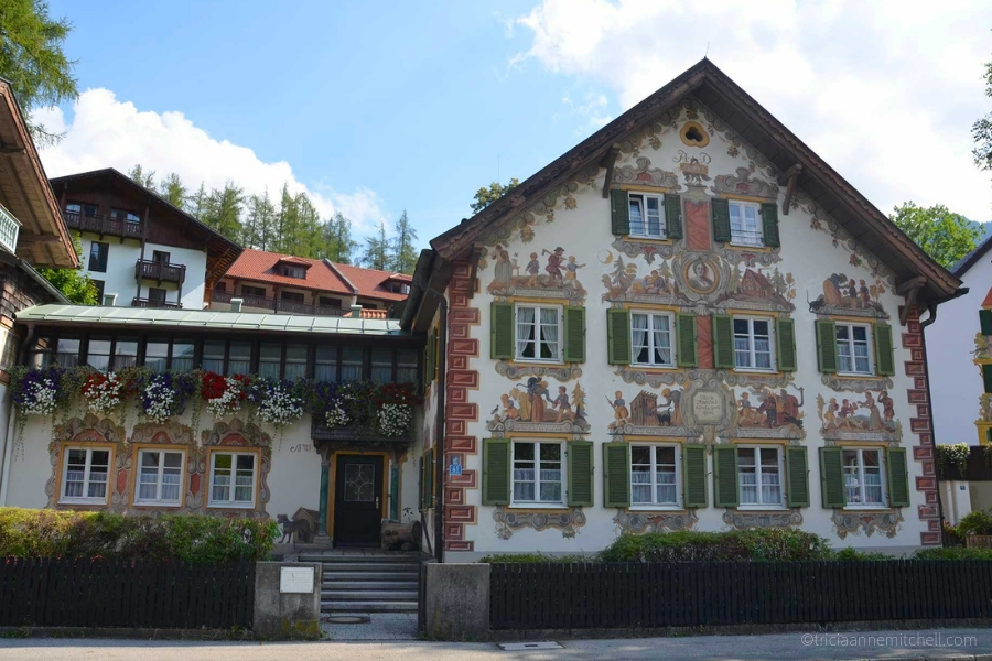 A building in Oberammergau, Germany is white, with green shutters, and elaborate murals telling the story of Hansel and Gretel.