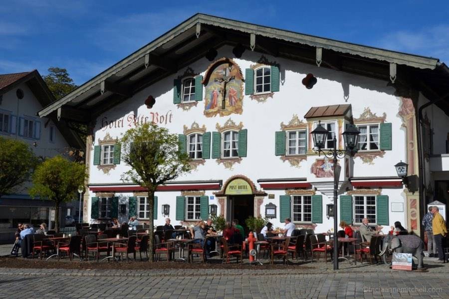 People at cafe tables sit in front of the Hotel Alte Post in Oberammergau, Germany on a sunny day. The sky is blue, and the building is painted with religious murals. The walls are white and the shutters are green.