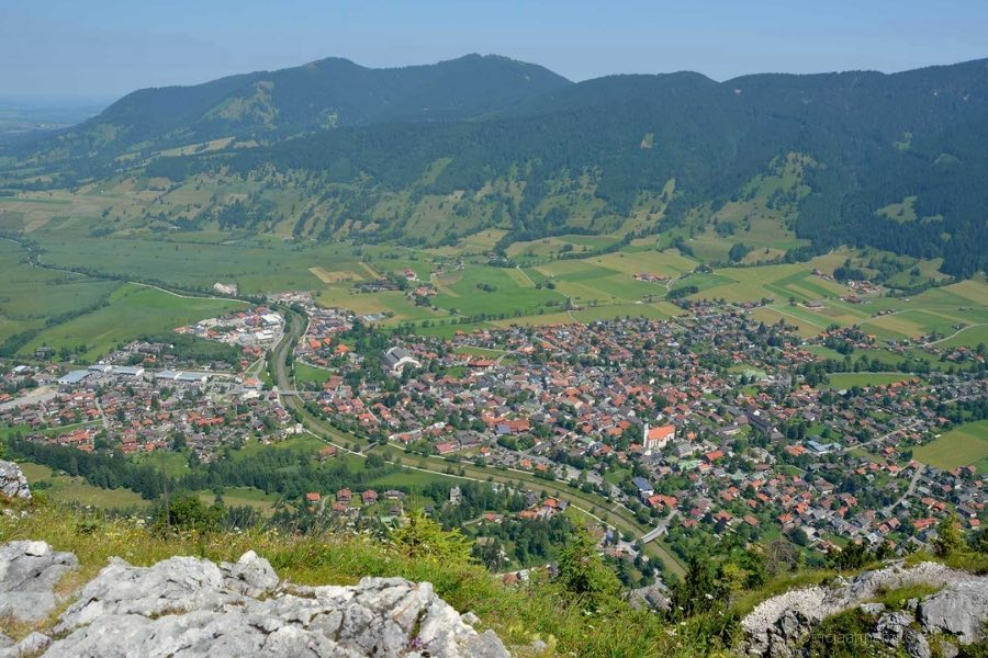 The village of Oberammergau is visible from the top of the Kofel Mountain in Germany. You can see red rooftops, the Ammer River, and green mountain slopes below.