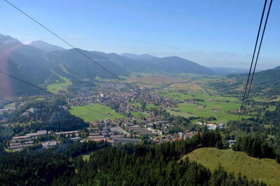 An aerial view of Oberammergau, Germany. The rooftops of buildings are visible, as are evergreen trees and mountain slopes. The sky is blue, and two cable car wires are visible, as the photo was taken from inside the gondola.