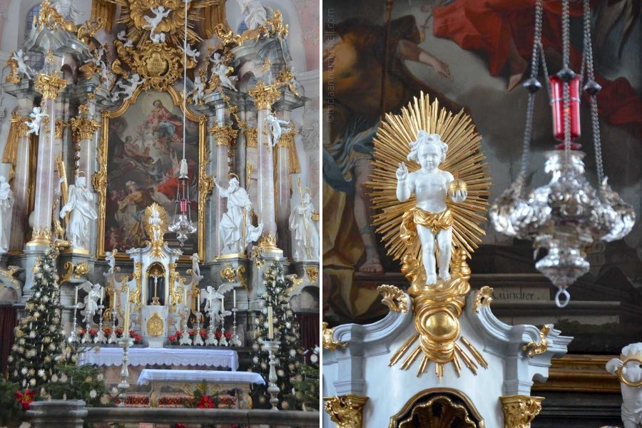 The altar of the Saint Peter and Paul Church in Oberammergau is decorated with 2 Christmas trees, silver candelabras, and poinsettia plants.