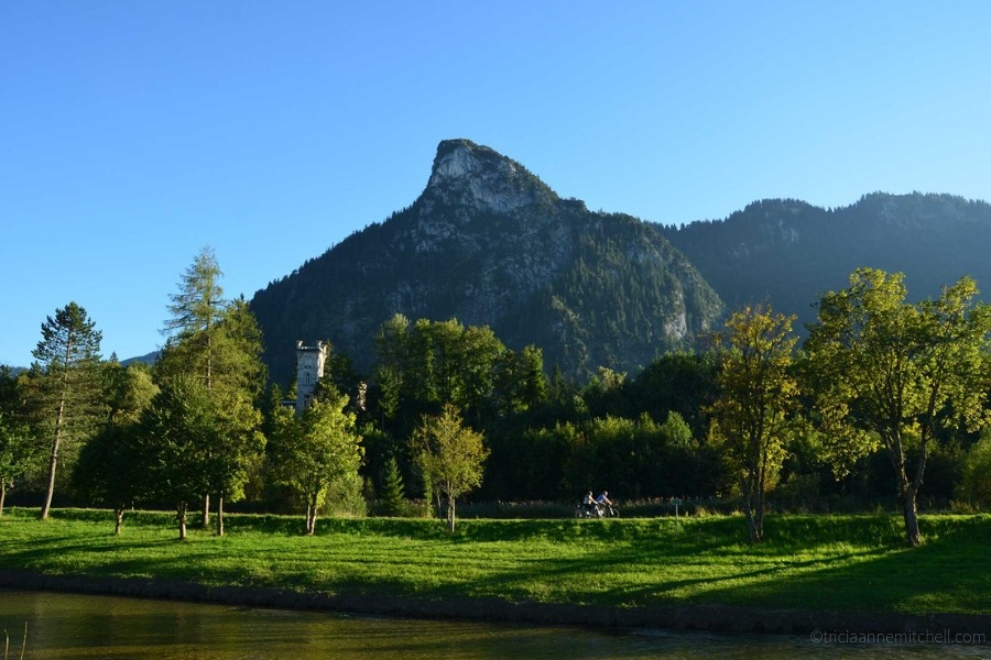 Two cyclists ride past a castle-like home and a river in Oberammergau, Germany. There is a mountain overhead.