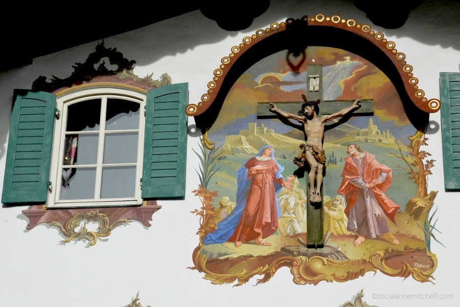 Close-up of a green-shuttered window in the German town of Oberammergau. A religious scene, complete with a crucifix, is also painted on the front of the building.