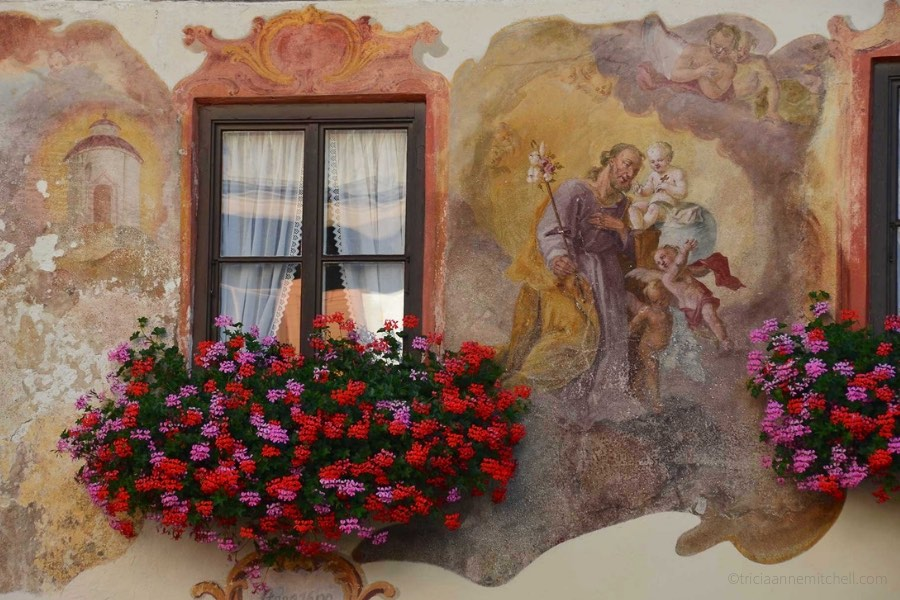 Detail of a home in Oberammergau, Germany: Red and pink flowers fill a flowerbox, alongside a religious mural.