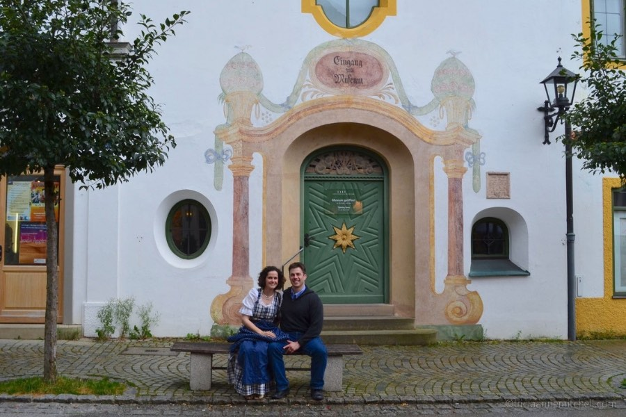 A couple sits in front of the entrance of Oberammergau's town museum.