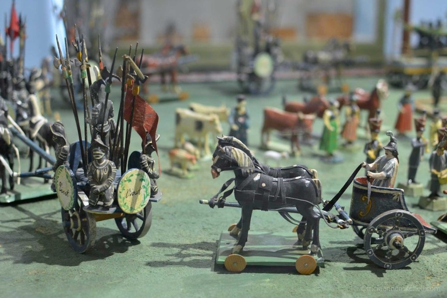 Model toy wagons and soldiers are on display on a green background inside the Oberammergau Museum.
