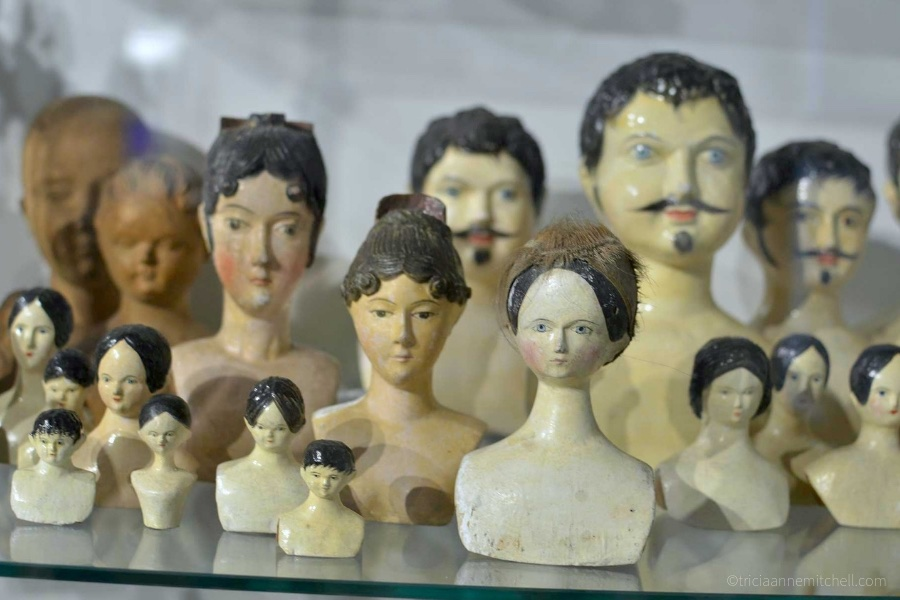 Antique doll heads of all sizes are on display on top of a glass shelf in the Oberammergau Museum in Germany.