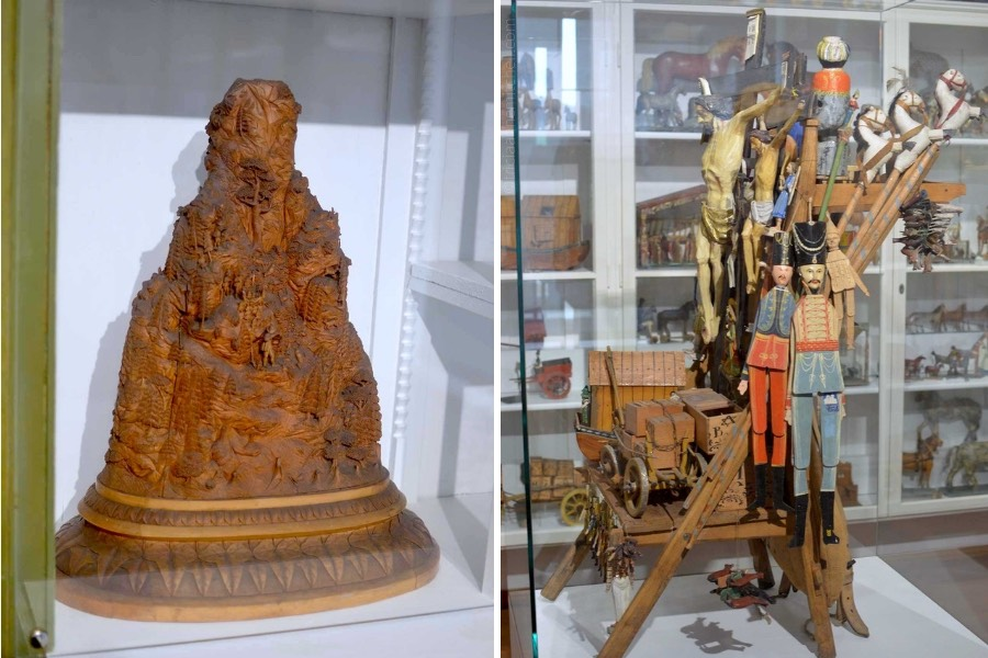 Items on display inside the Oberammergau Museum: on the left, a wooden, handcarved model of the Kofel Mountain. It sits inside a display case. On the right, a wooden