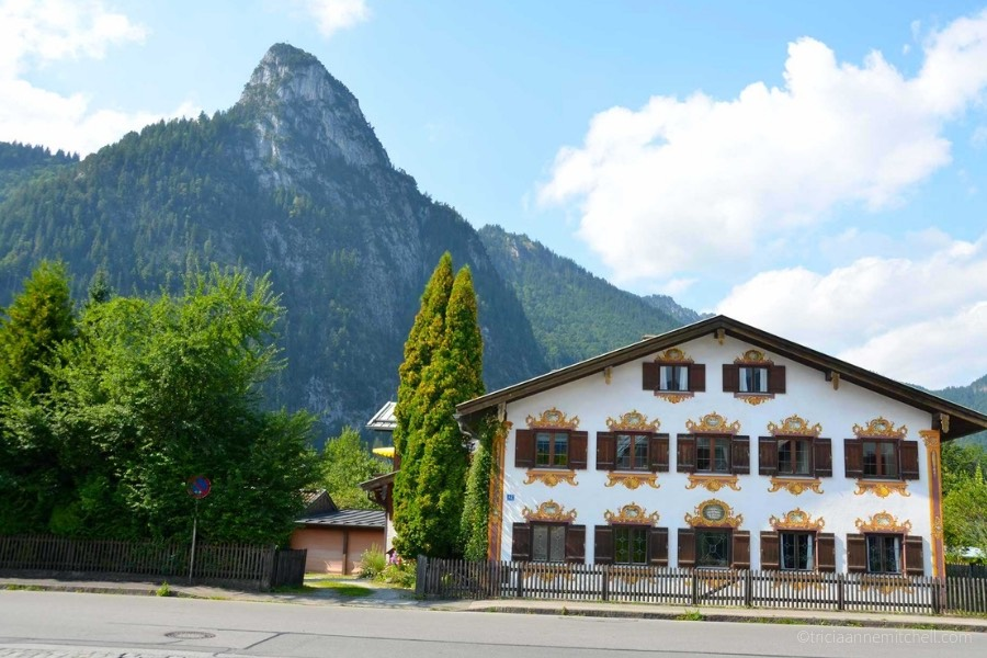 A mountain peak towers over a white, chalet-style home in Oberammergau, Germany.