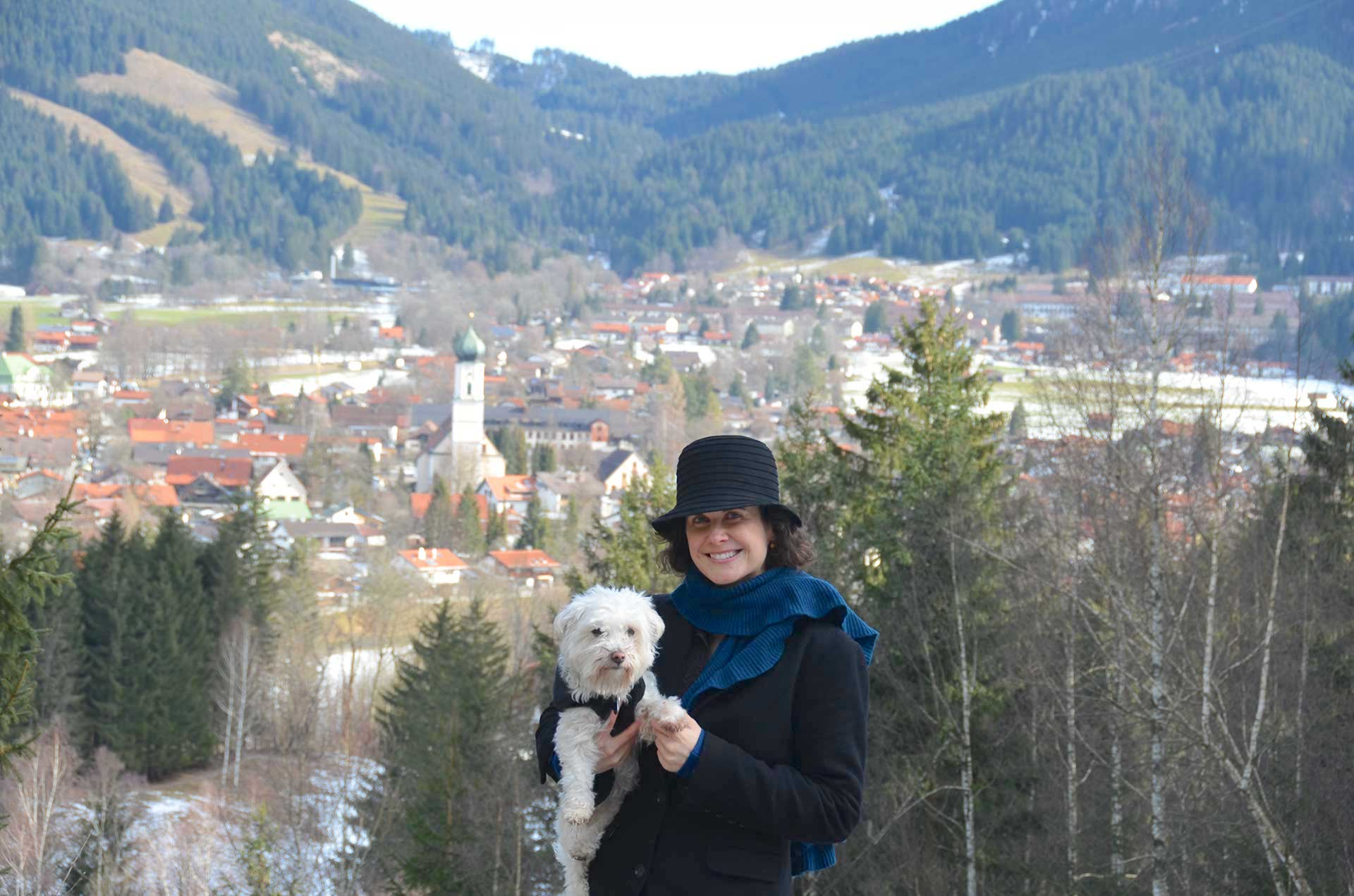 A woman holding a white dog stands outside in nature. The village of Oberammergau is visible behind her, as are forested mountain slopes.