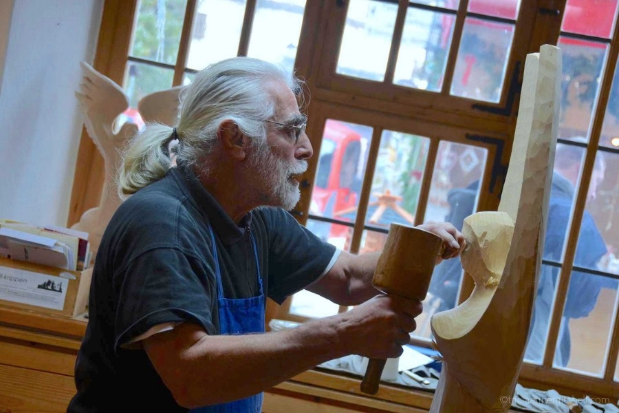 A man with a bear carves an angel out of a block of wood. He is working in front of a window, inside a workshop in Oberammergau, Germany.