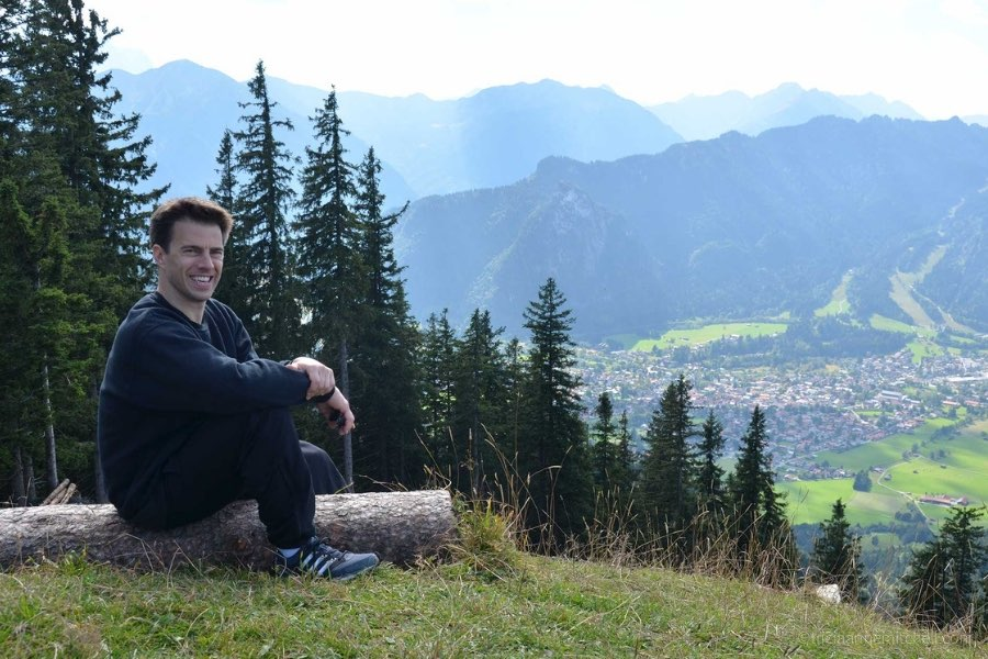 A man sits on top of a mountain slope, overlooking the village of Oberammergau, Germany below.