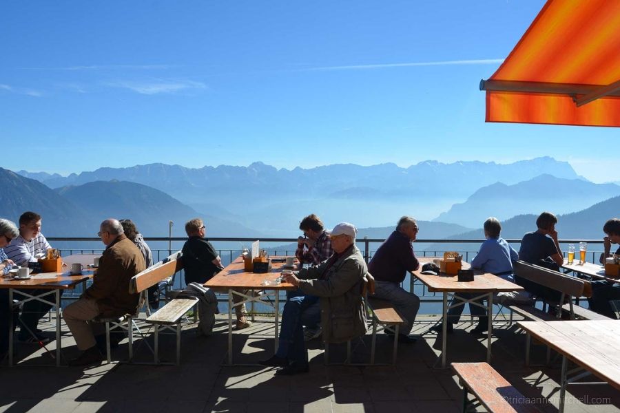 Sitting at tables on an outside terrace of the Laber Mountain's restaurant, people look out at the panoramic views. The sky is blue, and the corner of an orange umbrella is visible.