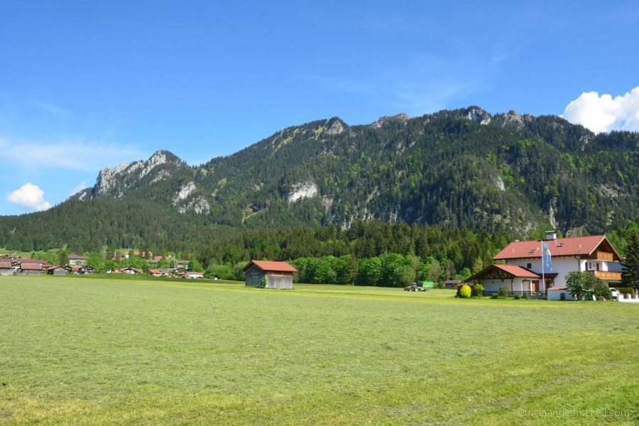 A forested mountain towers over a Bavarian house and wooden barn in the village of Oberammergau, Germany.