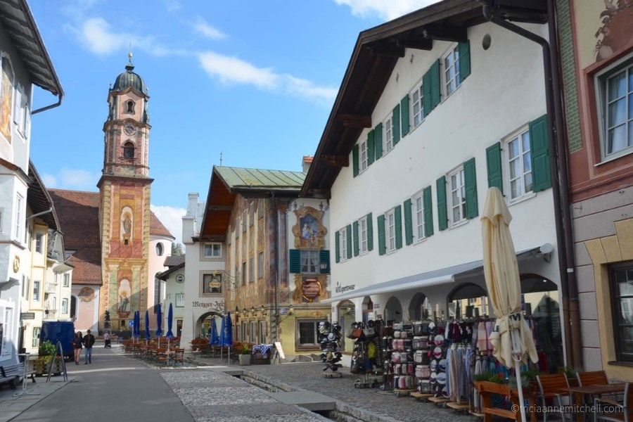 A Mittenwald, Germany street scene has painted, traditional buildings, a canal, and a church bell tower painted with frescoes.